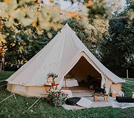 A luxury bridal suit bell tent with rugs and cushions outside