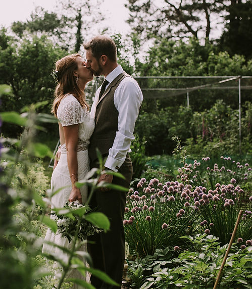 Bride and groom kissing in a garden of greens and purples