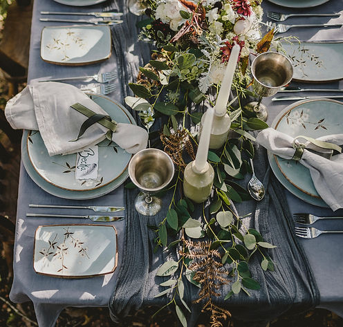 Outdoor wedding table with grey layerd linens, silver glasses, cream earthenware pots holding tall white candles, duckegg tableware with a floral design, a eucalyptus runner and white and deep red flowers.