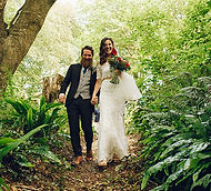 Bride and groom walking hand in hand through a forest