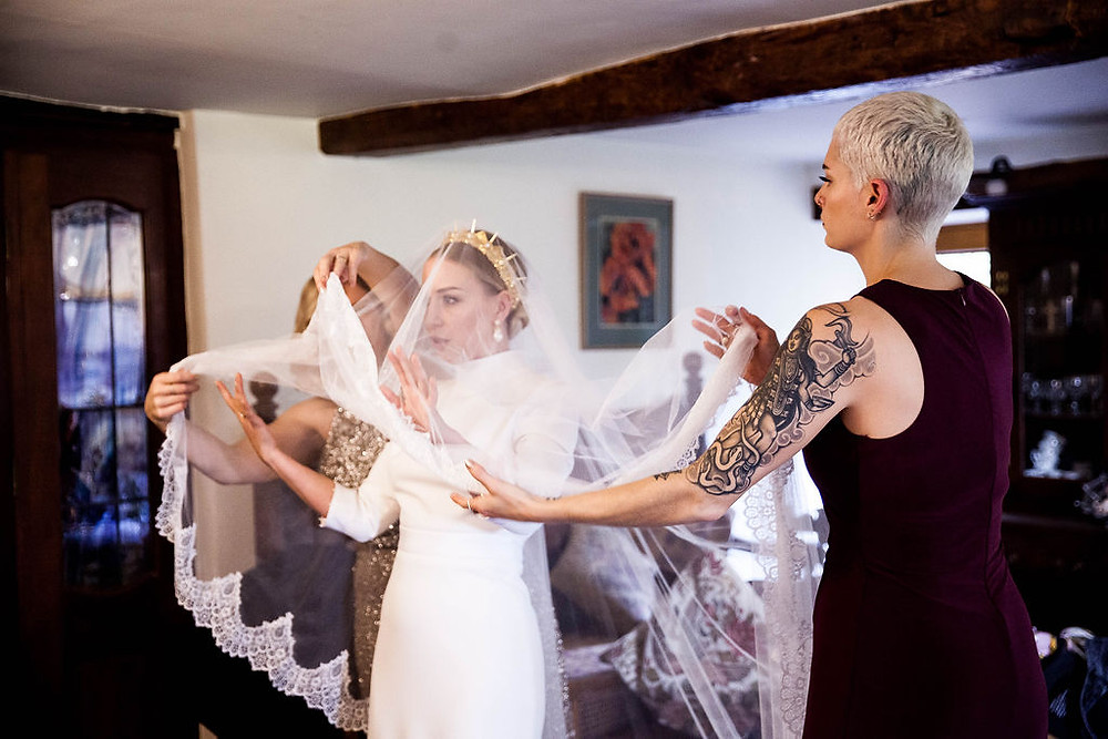 Two bridesmaids helping a bride put her veil on, the bride is wearing a golden crown, one bridesmaid has a tattoo on her arm. They are in a farmhouse in wooden beams.