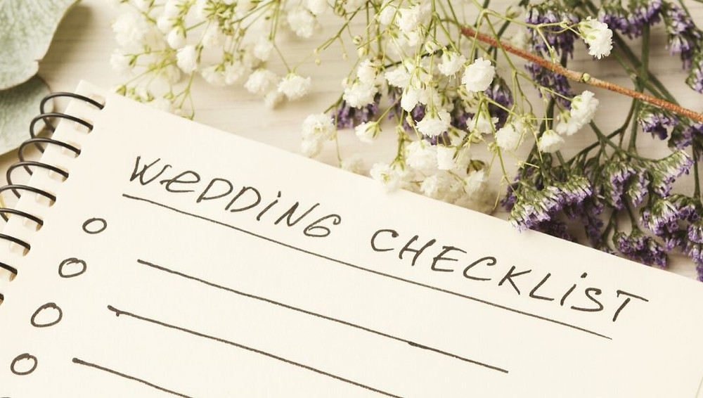 Wedding checklist hand written on a notebook with lavender and baby's breath sprigs lying on the table next to the notebook.