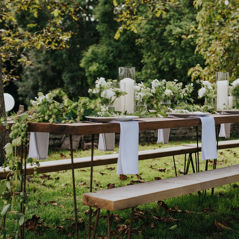 Outdoor wedding reception table decorated with greenery and white flowers, white napkins and pillar candles in hurricane lamps.