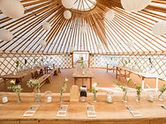 Inside a wedding yurt, the tables are laid with flowers and napkins