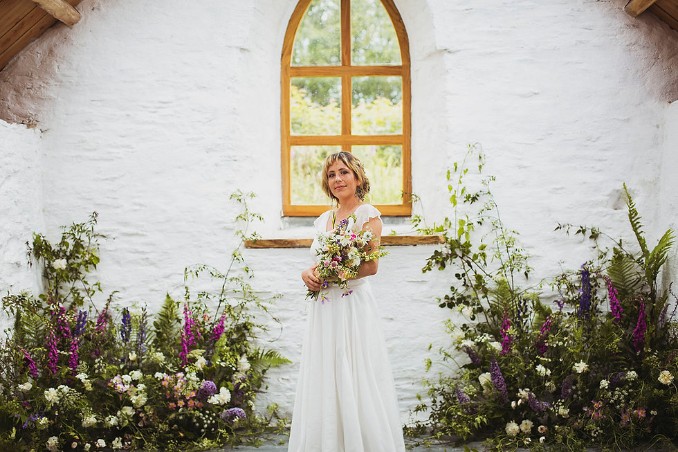 Bride holding wildflower bouquet in church with wildflower ceremony floristry