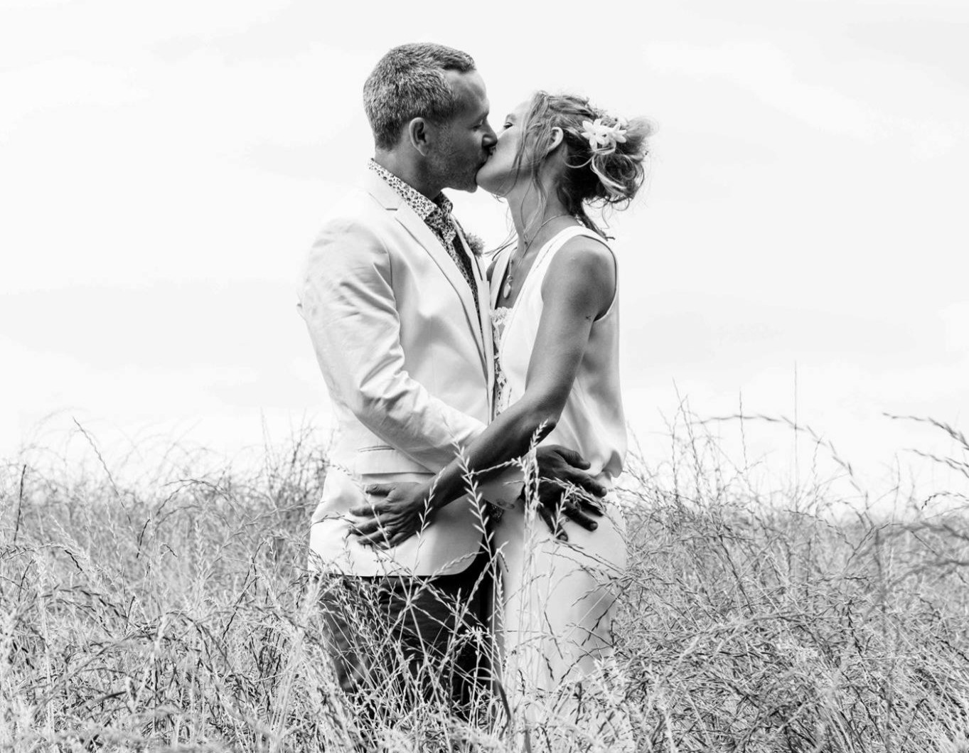 Bride and groom kissing in a meadow of tall grass.