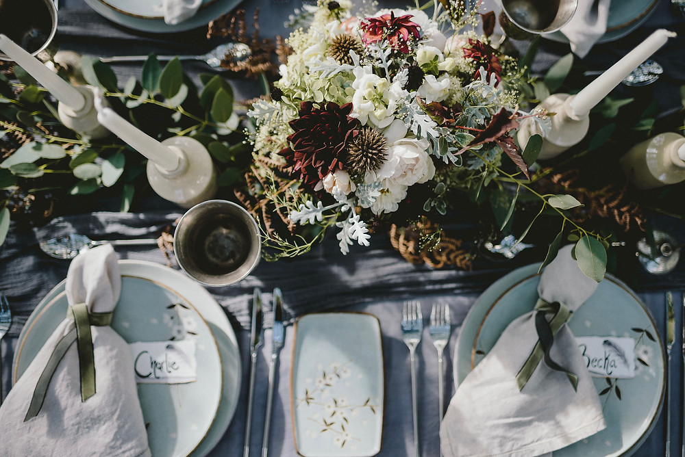Wedding table with layered linens in grey tones, silver glasses, cream earthenwear jars holding tall cream candles, auntumnal flowers in whites and deep reds and a eucaliptus runner. the tablewear is duckegg with white flowers, the napkins are tied with dark green ribbon, and the place names are hand painted with a watercolour feather.