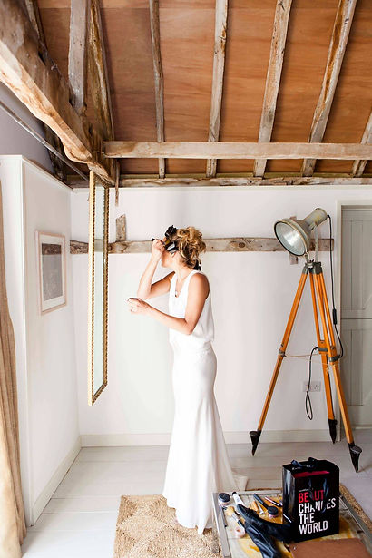Bride doing her makeup in a converted barn with white walls, wooden beams and painted wooden floor.