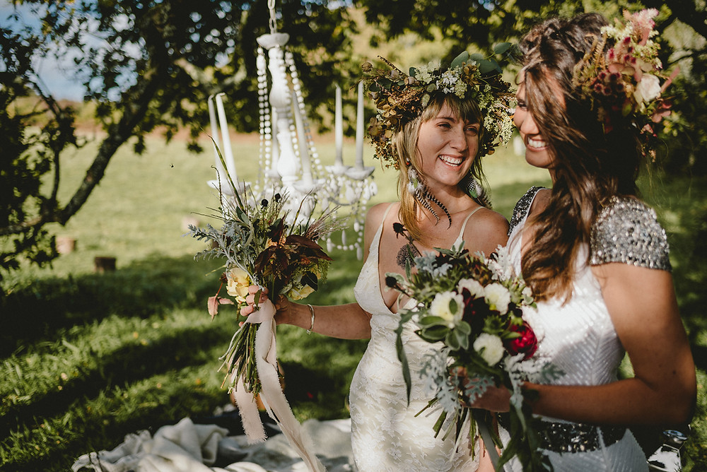 Two brides standing hand in hand under tree's. there is a white chandelier hanging behind them and they both have bouquets and floral crowns. They are laughing.