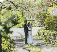 Brdie and groom standing together in the garden of a stately home