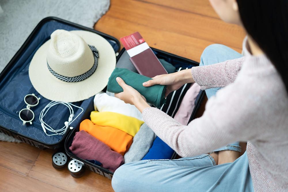 אישה יושבת מול מזוודה ואורזת חפצים של יציאה לחופשה