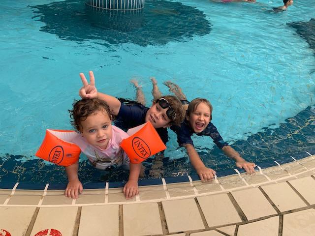 שלושה ילדים נהנים בבריכה