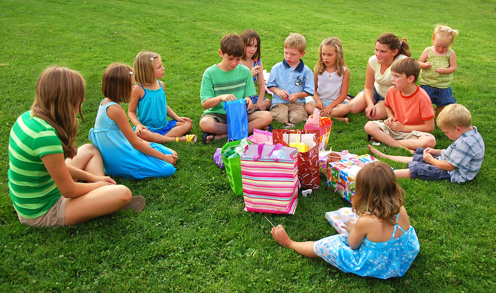 ילדים יושבים על הדשא ופותחים מתנות יומולדת