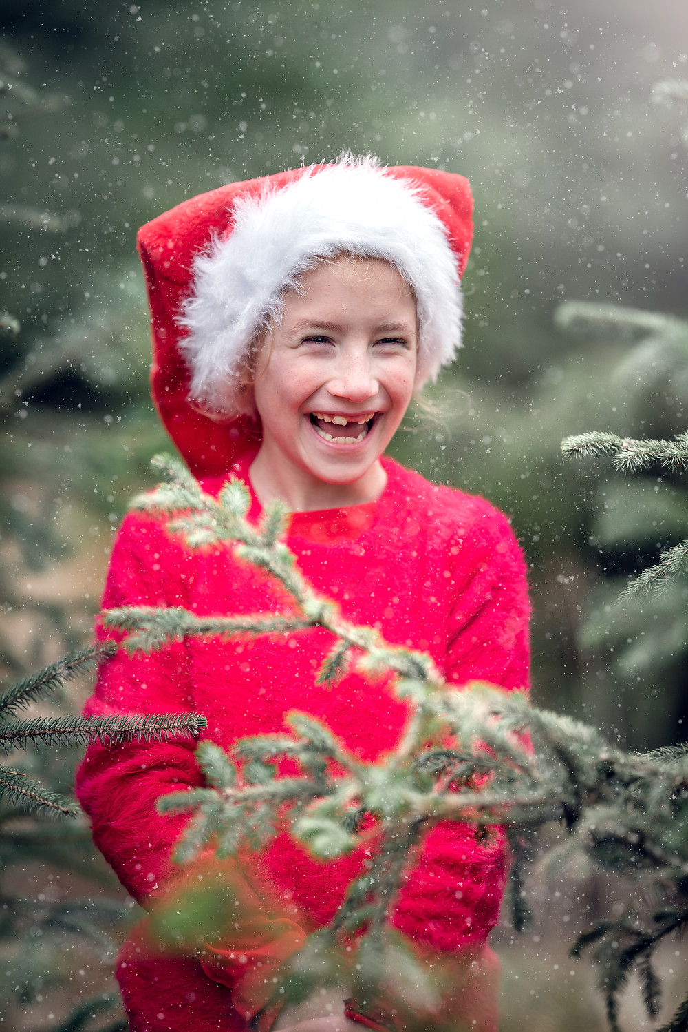 Girl among coifers in the snow. Outdoor Christmas photography by Somerset photographer Sarah Gibson