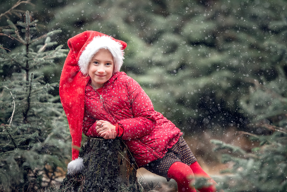 Girl in festive hat, in Somerset forest. Outdoor family photography by Somerset photographer Sarah Gibson