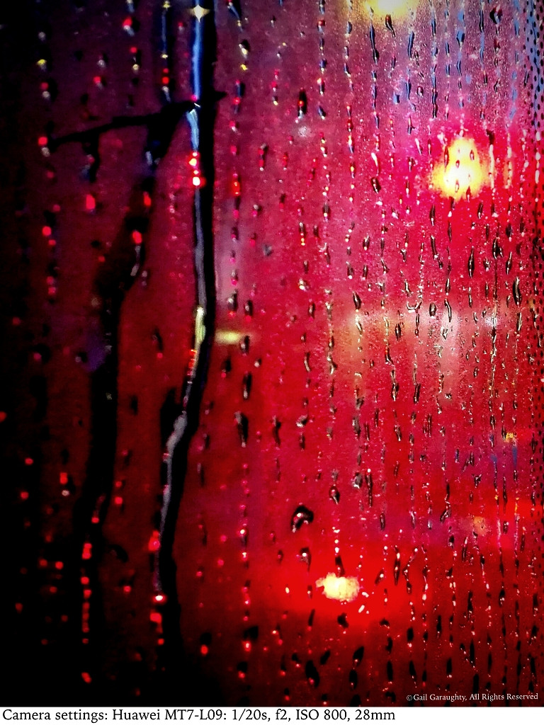 Rain from the inside of the bus window while stopped at a red light