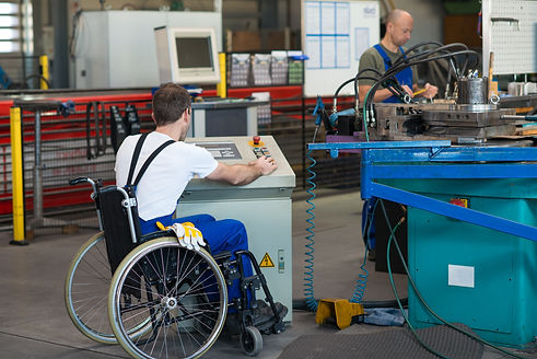 man in a wheelchair working at a factory