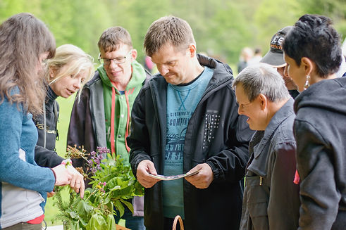 individuals with a visable disability looking at some plants that a woman is pointing at
