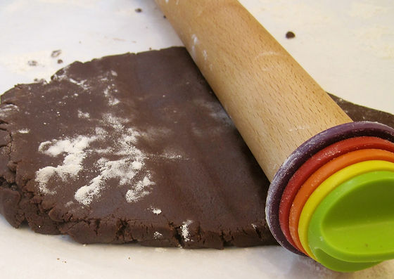 Wooden rollng pin with multicolor thickness rings rolling out chocolate sugar cookie dough.