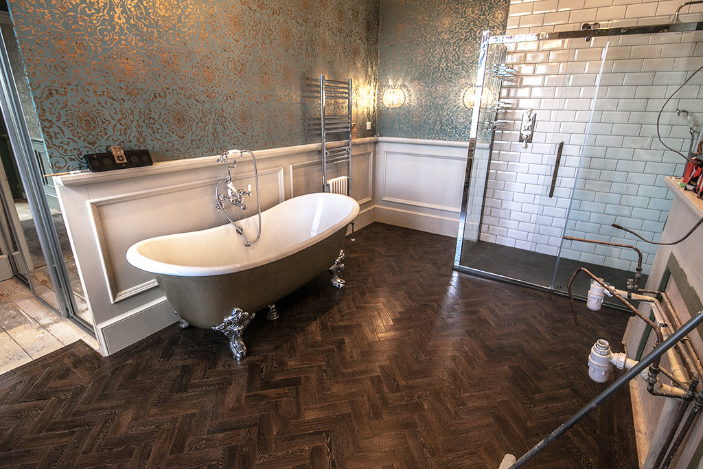 A stunning bath and dark parquet