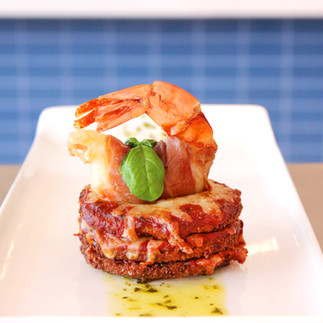 Prosciutto Wrapped Shrimp Stuffed with Scallop Mousse on an Eggplant Parmigiana