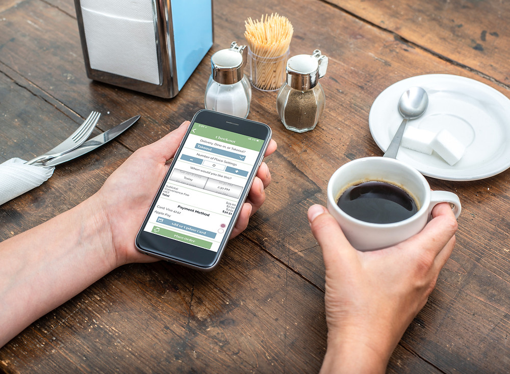 Phone with Valley Eats App on it held in left hand. Right hand is holding a coffee.