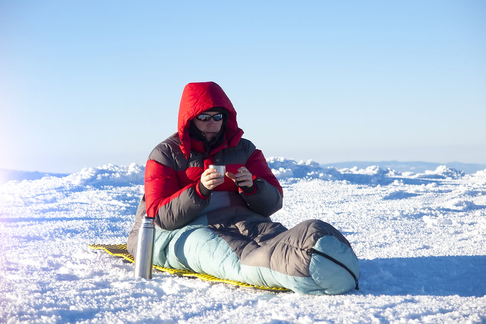 A man sits in a sleeping bag and drinkin