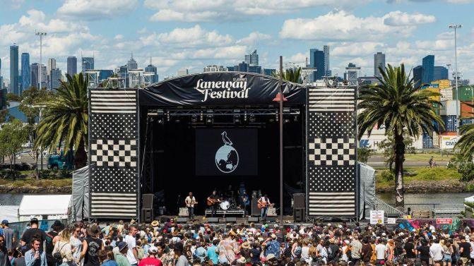 A crowd gathers in front of a black stage with Laneway Festival written in front.