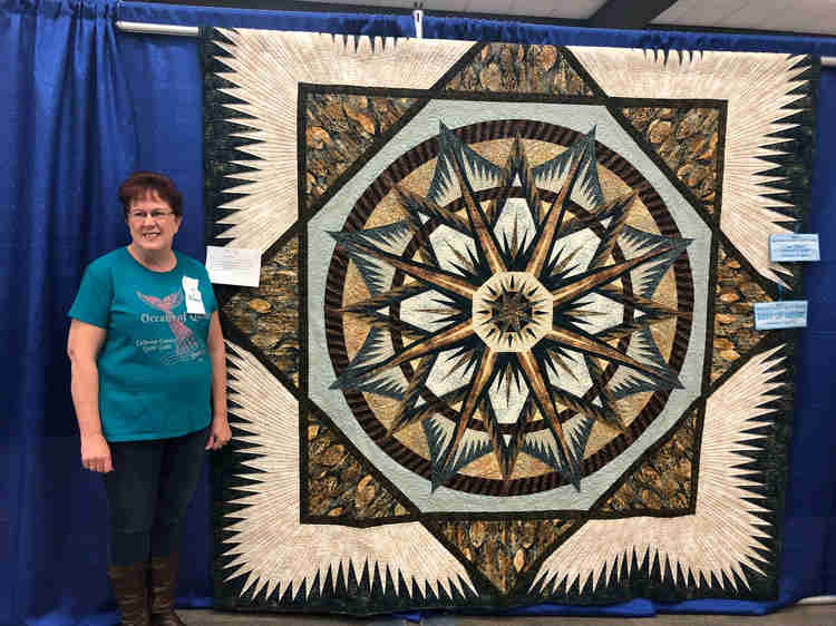 Woman standing by brown and tan geometric quilt