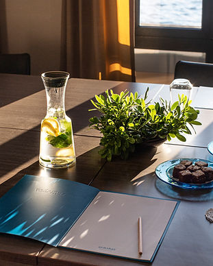 Meeting room with notepad and refreshments overlooking the sea.