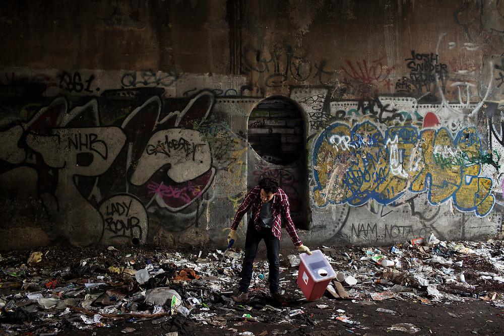 Un trabajador de la iglesia de Santa Ana recoge jeringas usadas en un túnel al sur del Bronx. Credit Carlos Villalón
