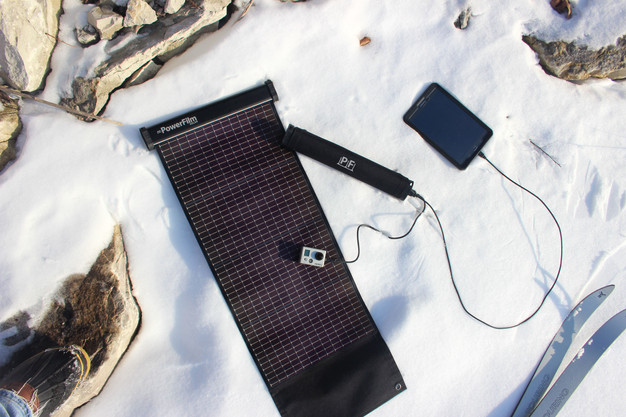 One LightSaver Max Portable Solar Charger unrolled in the snow and another rolled up charging a cell phone and a GoPro