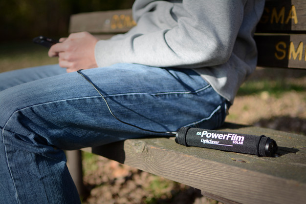 LightSaver Portable Solar Charger rolled up on a bench charging a cell phone