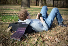 LightSaver Portable Solar Charger unrolled on the ground while man laying down uses his cell phone