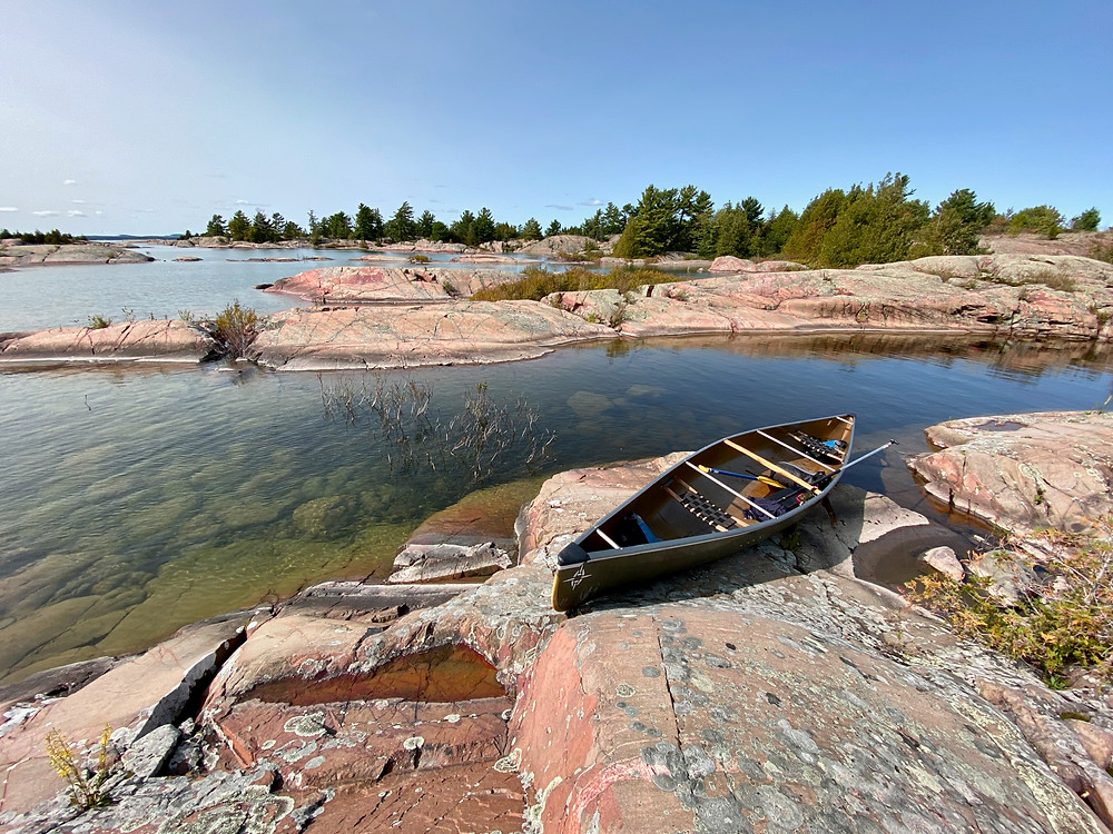 Daytime picture of the Georgian bay with pinkish rocks, water, and a canoe