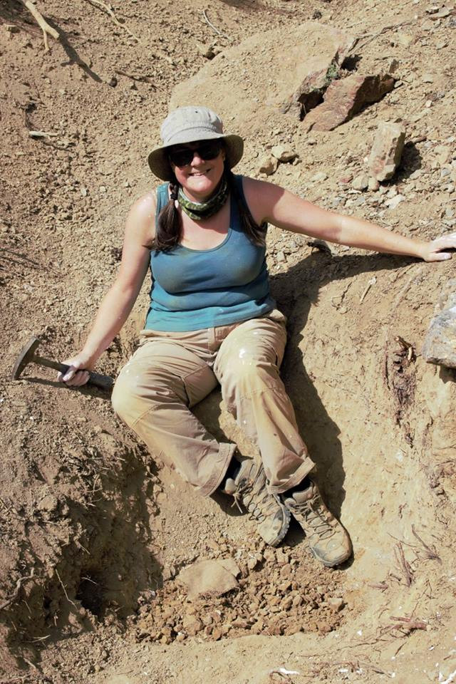 Picture of a female identifying person in the desert. She is sat on the edge of a ditch she has been digging into for fossils. In her right hand is a rock hammer. She wears a cream, fabric, sunhat and has dark sunglasses on. She is also wearing a green bandana, blue tank top and tan field trousers that are spotted with plaster and mud from digging. She is wearing dusty walking boots.