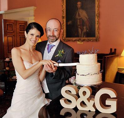 happy bride and groom cutting wedding cake Wedderburn Castle in the Borders, Scotland