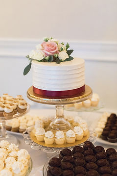 wedding cake with fresh flowers and cupcakes wedding dessert table