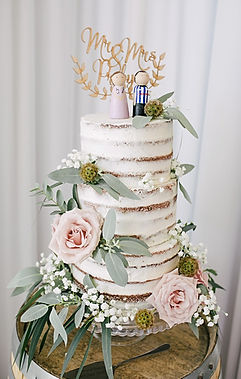 naked floral wedding cake with gold wedding topper