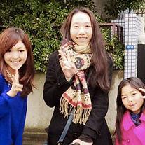 家の外でほほ笑む留学生と子供