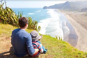 丘から海を眺める親子