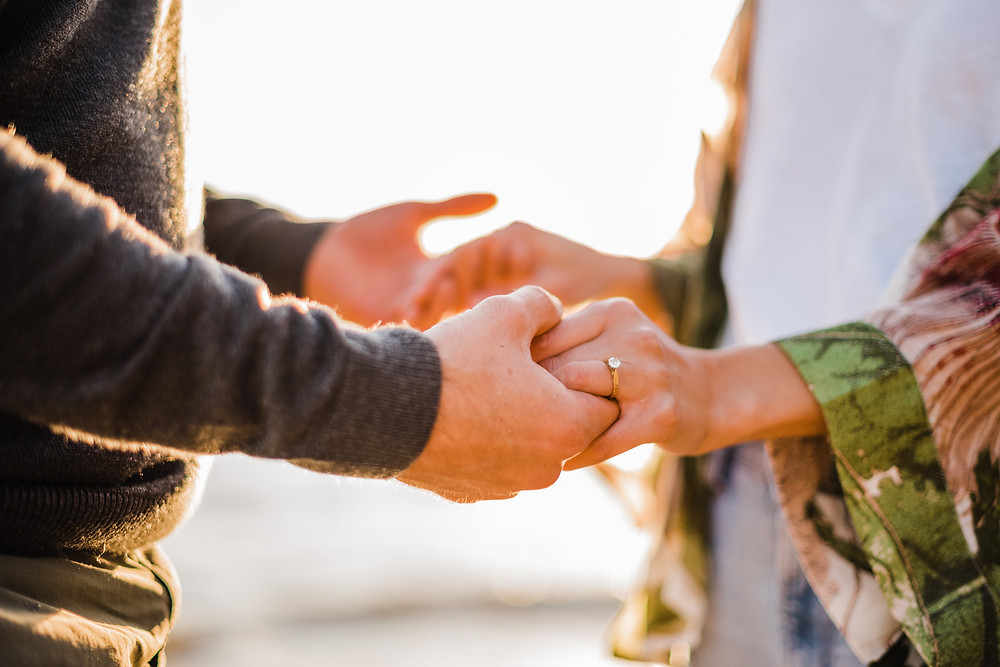 couple holding hands showing engagement ring