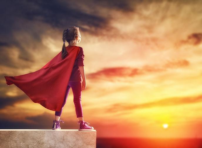Little child plays superhero. Kid on the background of sunset sky. Girl power concept.jpg