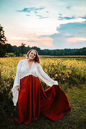 Coty Danyelle wearing a burgandy dress in front of a sun flower field.