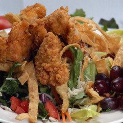 Santa Fe Chicken Salad: Crispy Chicken Strips served with Mixed greens, crumble bacon, diced tomatoes and shredded Monterrey Jack cheese with a home-made honey mustard dressing.