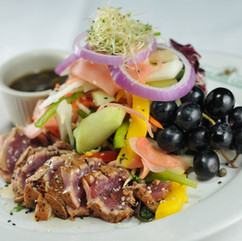 Tuna Salad: Sashimi-grade tuna seared, sliced and served over Asian Vegetables tossed in a home-made Dijon vinaigrette.
