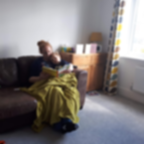 Adult and child cuddling on sofa, reading together
