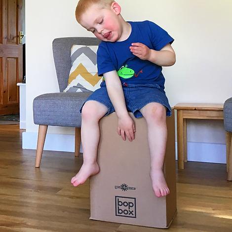 Child drumming on cardboard box