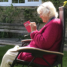 Lady sat in garden looking at her phone