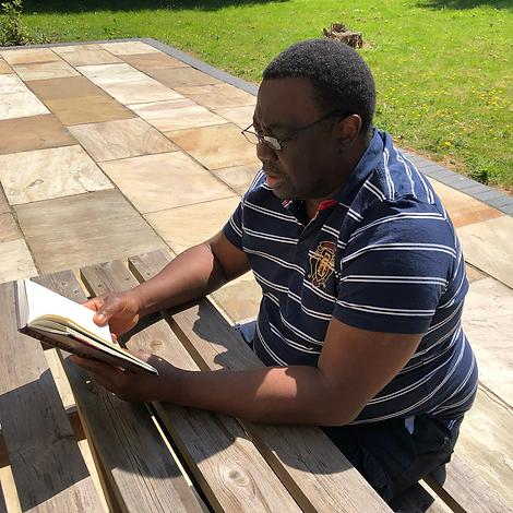 Man sat at sunny picnic bench reading a book